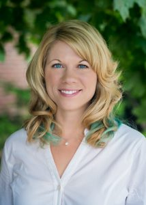 Morgan busse, author. blonde with aqua highlights and a great smile, in front of some trees