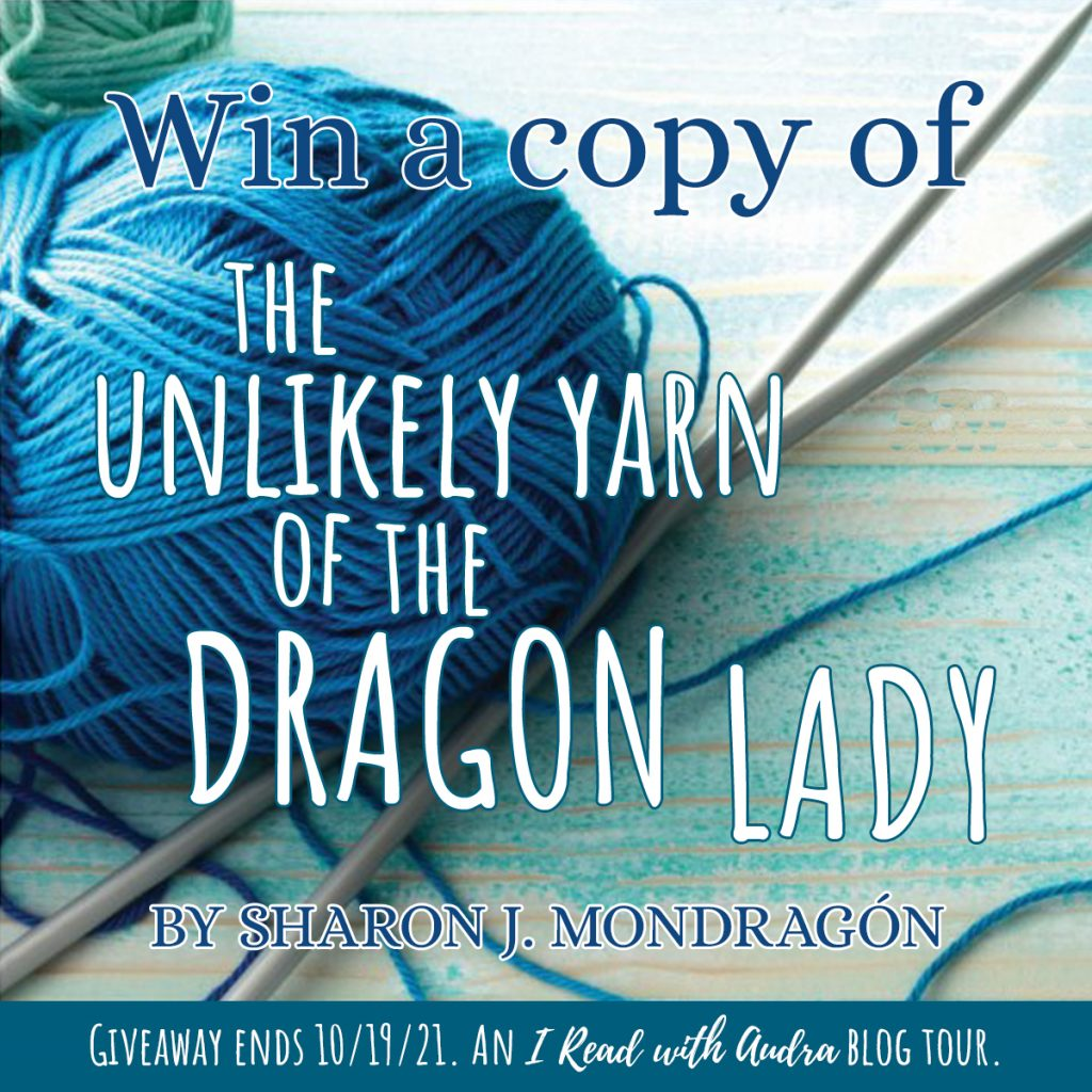 Win a Copy of The unlikely yarn of the dragon lady, by Sharon J Mondragon.  Giveaway ends 10/19/21. Blue/brown table with blue yarn and knitting needles