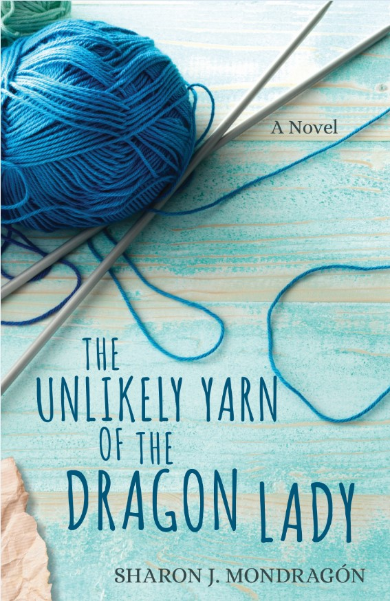 The unlikely yarn of the dragon lady, by Sharon J Mondragon. Blue/brown table with blue yarn and knitting needles